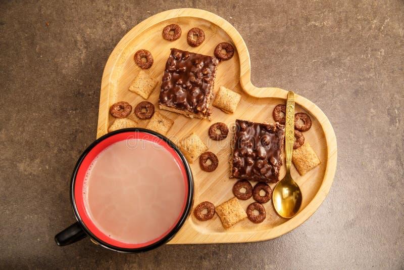 Waffles e cookies do chocolate em uma bandeja de madeira na forma de um coração e de um copo do chocolate quente imagem de stock
