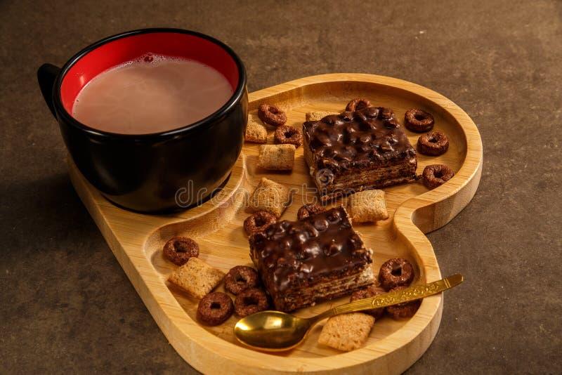 Waffles e cookies do chocolate em uma bandeja de madeira na forma de um coração e de um copo do chocolate quente fotografia de stock