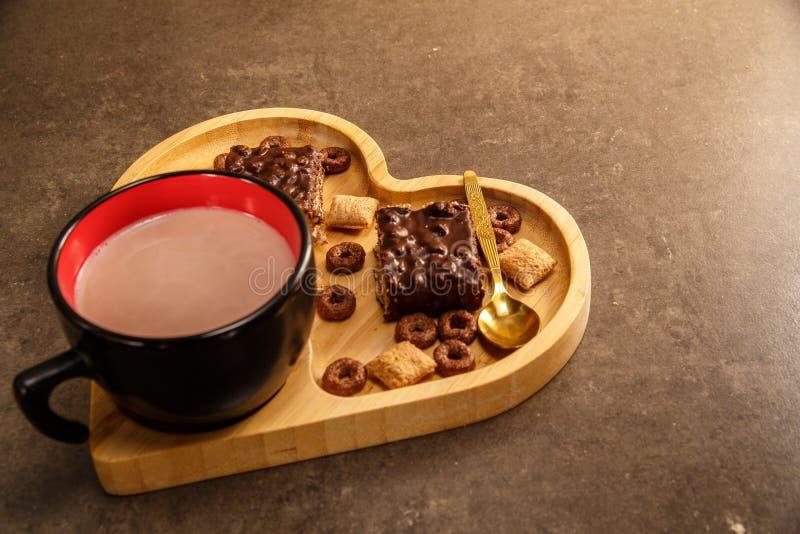 Waffles e cookies do chocolate em uma bandeja de madeira na forma de um coração e de um copo do chocolate quente fotos de stock royalty free