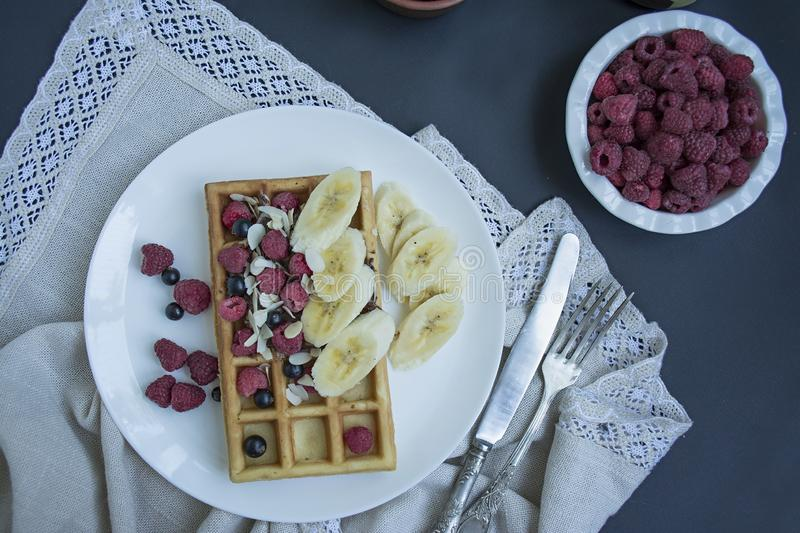 Waffles with fresh banana, raspberries, blueberries for breakfast. Belgian waffles. Dark wooden background stock photography
