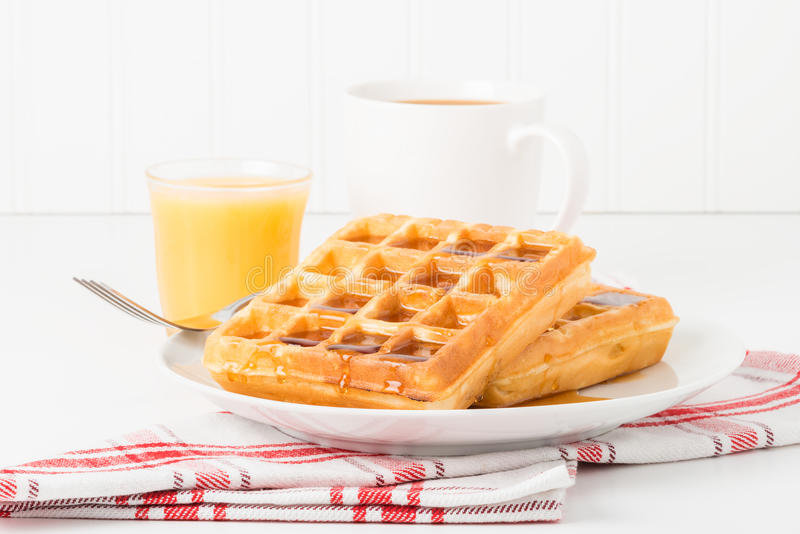 Waffles. Fresh made waffles and maple syrup served with juice and coffee royalty free stock photos