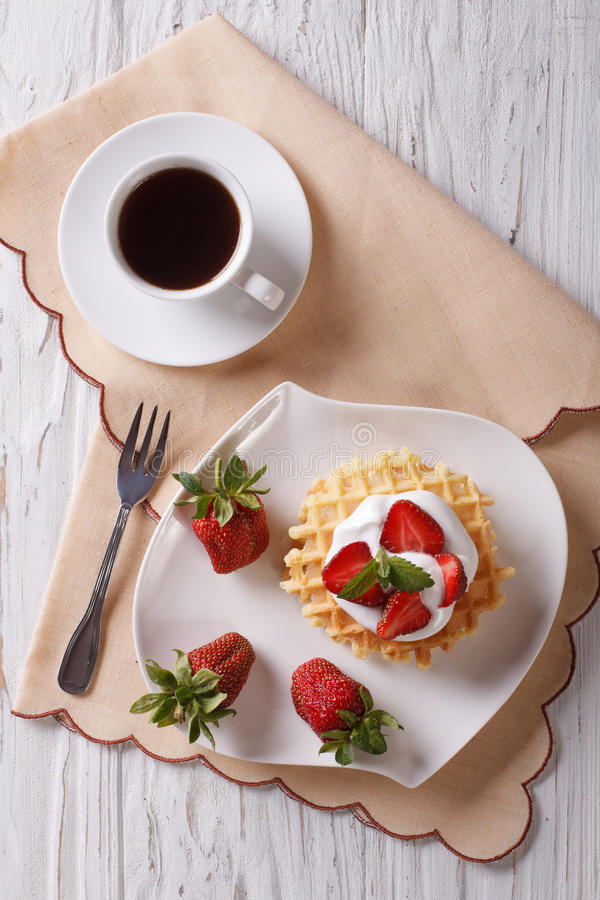 Waffles with fresh strawberries and coffee. vertical top view. Waffles with fresh strawberries, cream and coffee on a table. vertical top view stock image