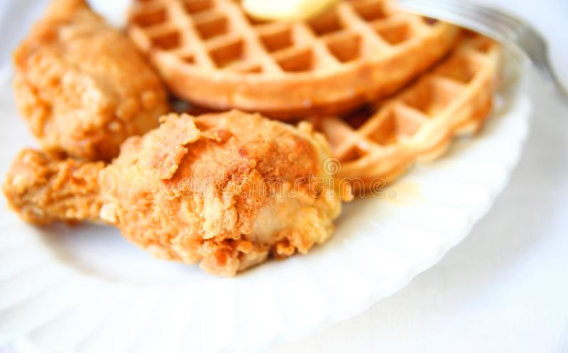 Waffles and fried chicken. Belgian waffles and fried chicken on a white platter with copy space royalty free stock image