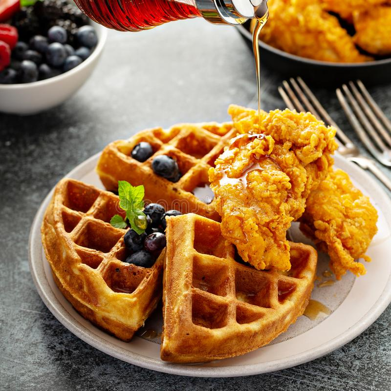 Waffles with fried chicken. And maple syrup, southern comfort food royalty free stock images