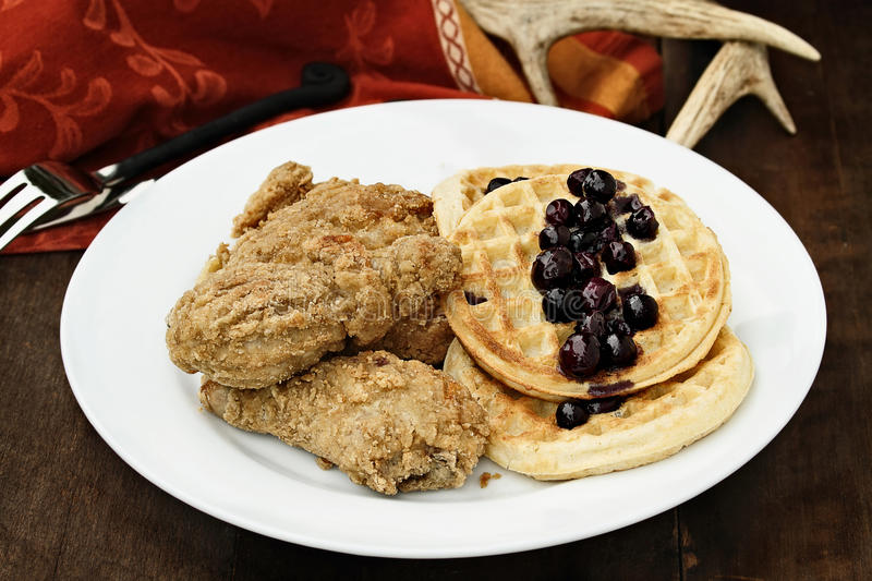 Waffles and Fried Chicken. Three pieces of deep fried chicken with waffles served with fresh blueberry sauce over a rustic background. Extreme shallow depth of stock images