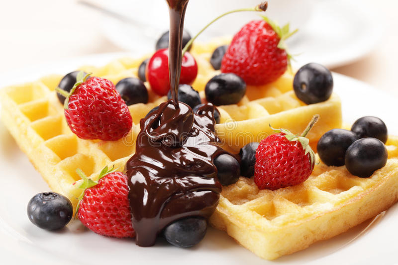 Waffles with fruits. Belgian waffles with strawberry, cherry, blueberry, and chocolate sauce stock image