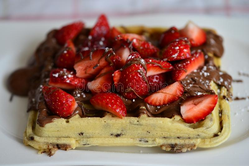Waffles. Homemade waffles with chocolate and strawberries royalty free stock photo