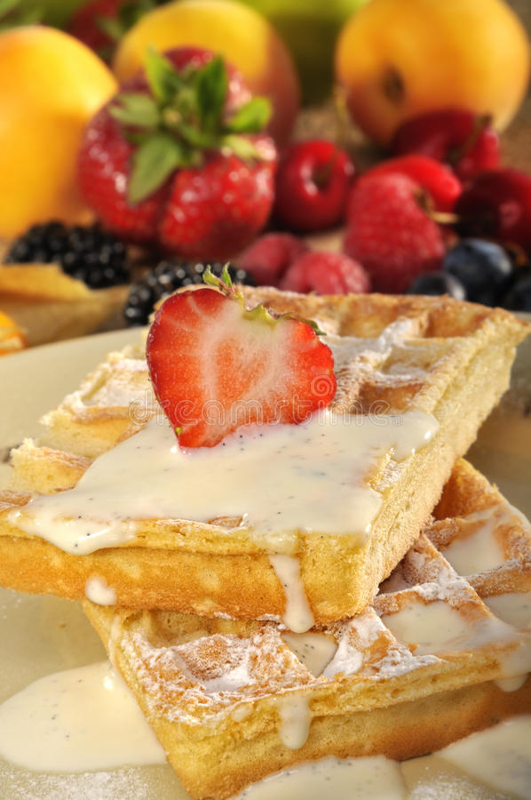 Waffles with ice cream. Appetizing waffles covered with vanilla iced cream and topped with strawberry, fruits in background royalty free stock photography