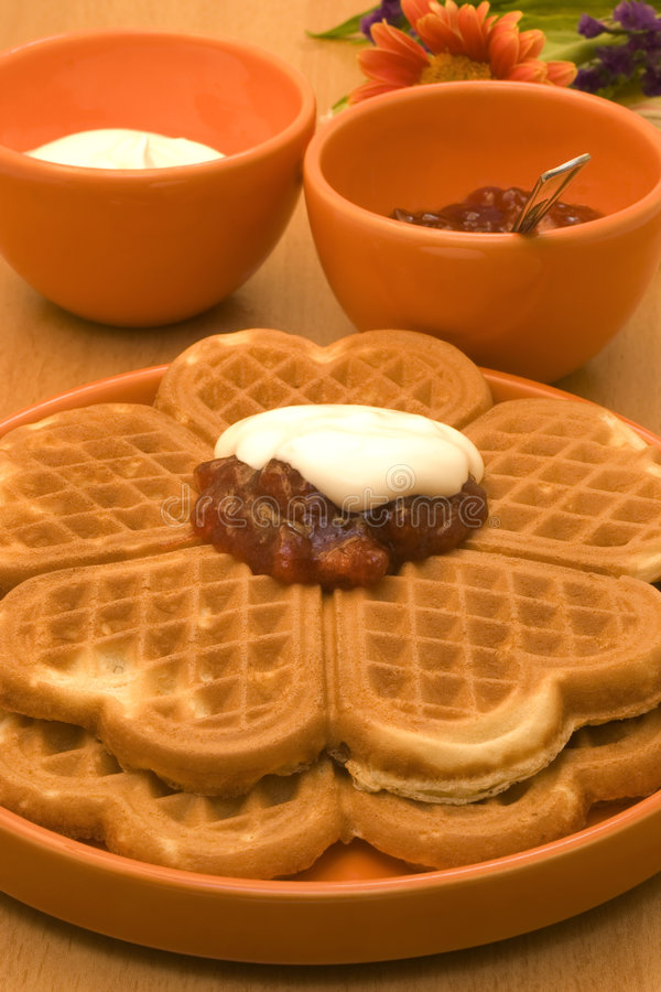 Waffles with jam. Waffles, jam and whipped cream in orange autumn colors royalty free stock images