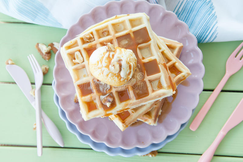 Waffles a la mode. Waffles with ice cream, caramel sauce and walnuts royalty free stock photo