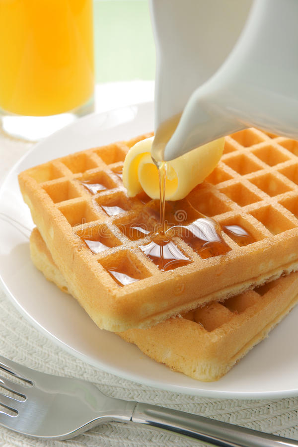 Waffles and maple syrup. Pouring maple syrup on a stack of waffles stock images