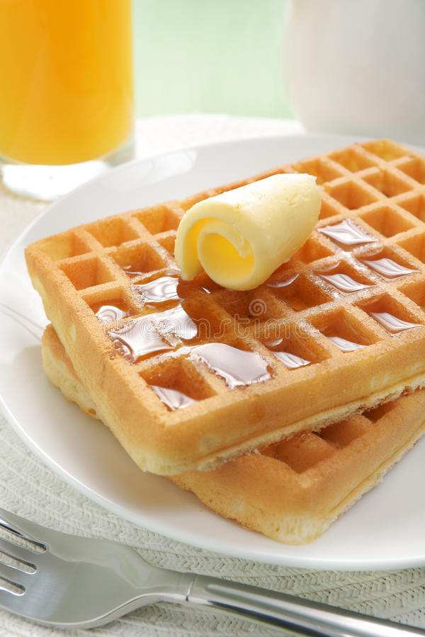 Waffles and maple syrup. Maple syrup on a stack of waffles stock photo