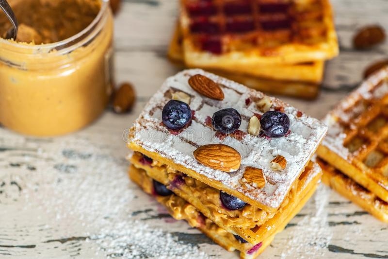 Waffles with peanut butter and blueberry berries on light wooden table. Close up, Selective focus stock images