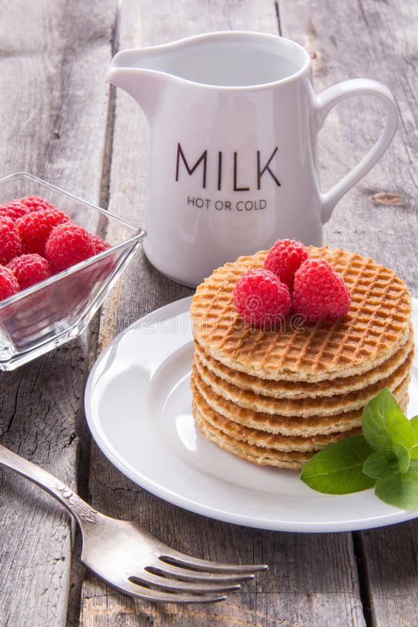 Waffles with raspberries for breakfast on a wooden table. Waffles with raspberries for breakfast stock photo