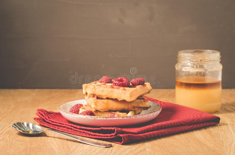 Waffles With raspberry in plate. Breakfast/Homemade waffles with raspberry, honey in plate on a old wooden table, selective focus. Dessert, berries, yummy stock photography