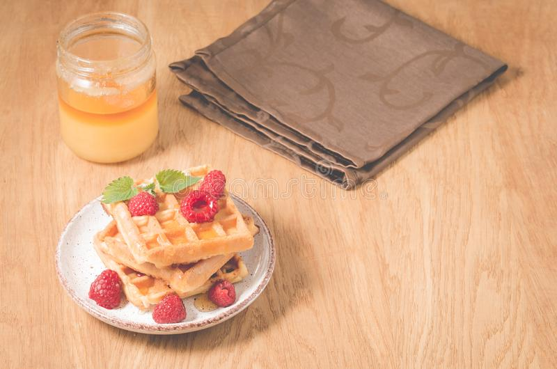 Waffles With raspberry in plate. Breakfast/Homemade waffles with raspberry in plate, honey on a wooden table, selective focus. Dessert, berries, yummy stock photography