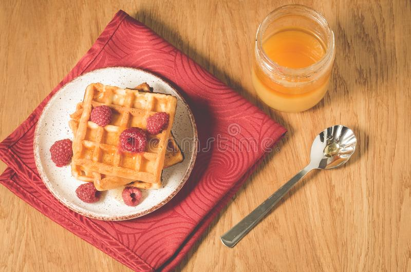 Waffles With raspberry in plate on a red napkin/waffles with raspberry in plate on a red napkin, and jar of honey. Top view. Breakfast, dessert, berries, yummy stock images