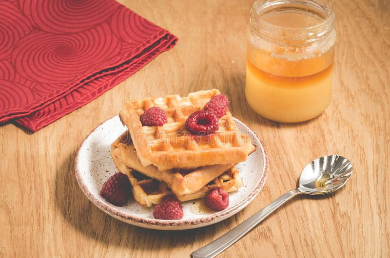 Waffles With raspberry in plate on a red napkin/waffles with raspberry in plate on a red napkin, and jar of honey on a wooden. Table, breakfast, dessert royalty free stock images