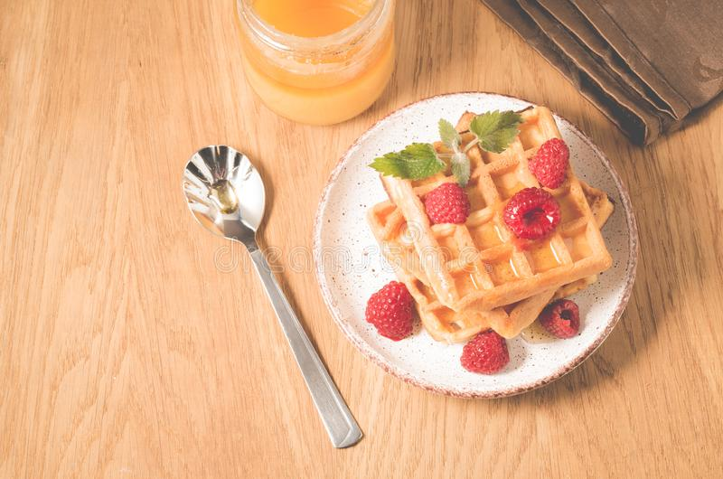 Waffles With raspberry in plate. Sweet dessert menu. Breakfast/Homemade waffles with raspberry, honey in plate on a old wooden. Table, top view, berries, yummy stock images