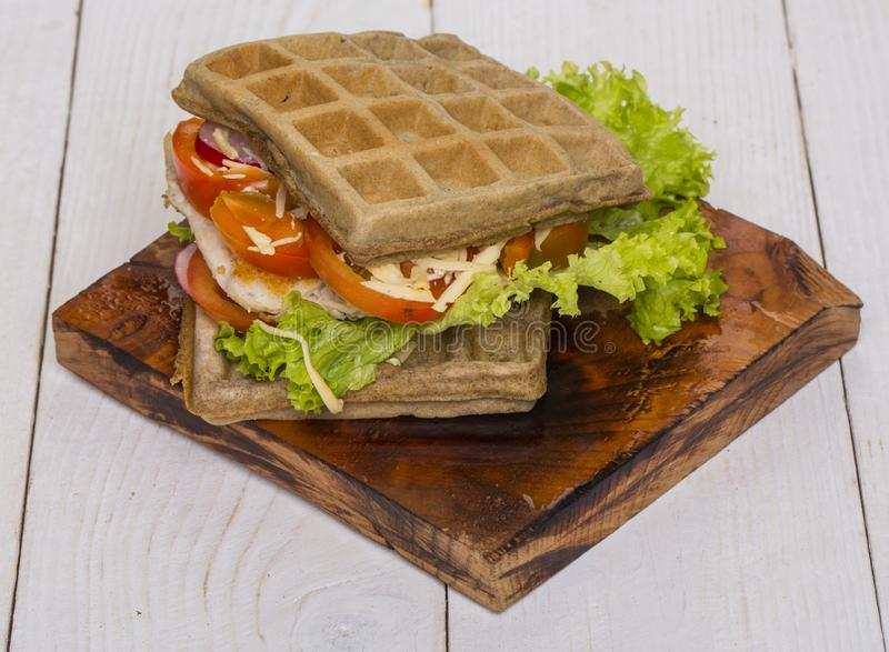 Waffles sandwich with chicken, vegetables and cheese on wooden background stock images