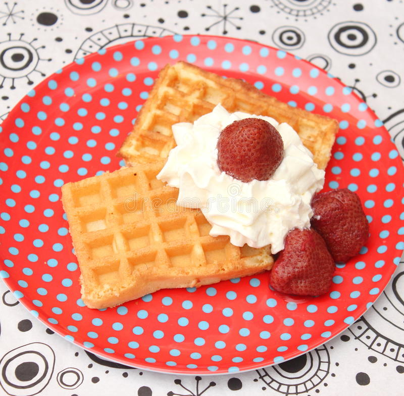 Waffles. Some waffles with cream and strawberries royalty free stock image