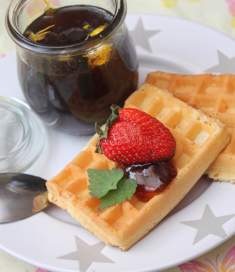 Waffles. Some homemade waffles with honey and strawberries stock photos