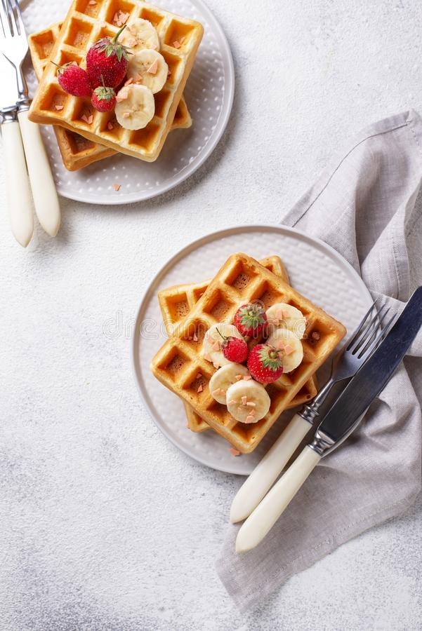 Waffles with strawberries and banana. Belgium waffles with strawberries and banana royalty free stock photo