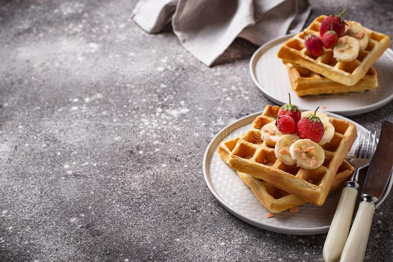 Waffles with strawberries and banana. Belgium waffles with strawberries and banana royalty free stock photography