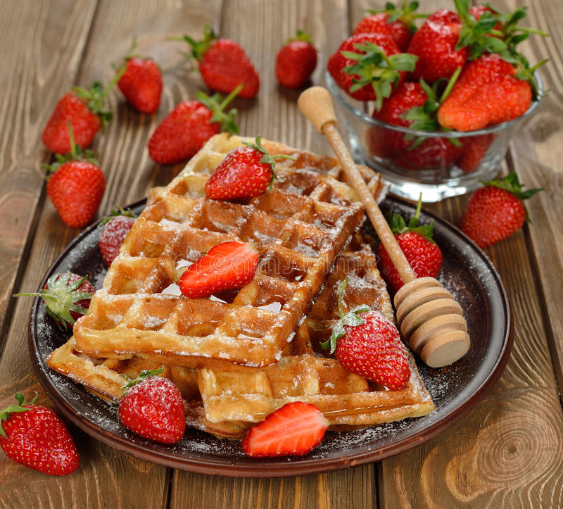 Waffles with strawberries. On brown background royalty free stock photo