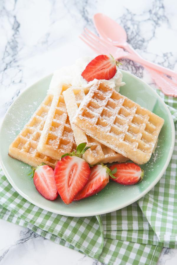Waffles with strawberries. Homemade waffles with fresh strawberries and whipped cream stock images