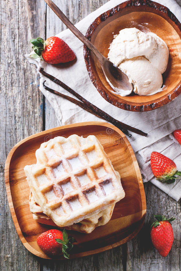 Waffles with strawberries and ice cream. Top view on wooden plate with fresh belgian waffles and bowl of ice cream, served with strawberries and vanilla sticks royalty free stock photography