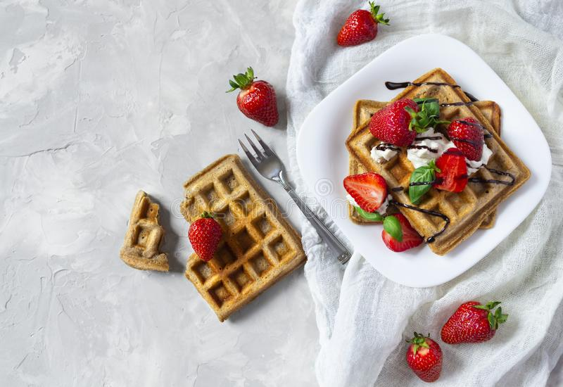 Waffles with strawberries, ricotta cheese and chocolate on white plate. Top view. Homemade square Belgian waffles with strawberries, ricotta cheese and stock photos