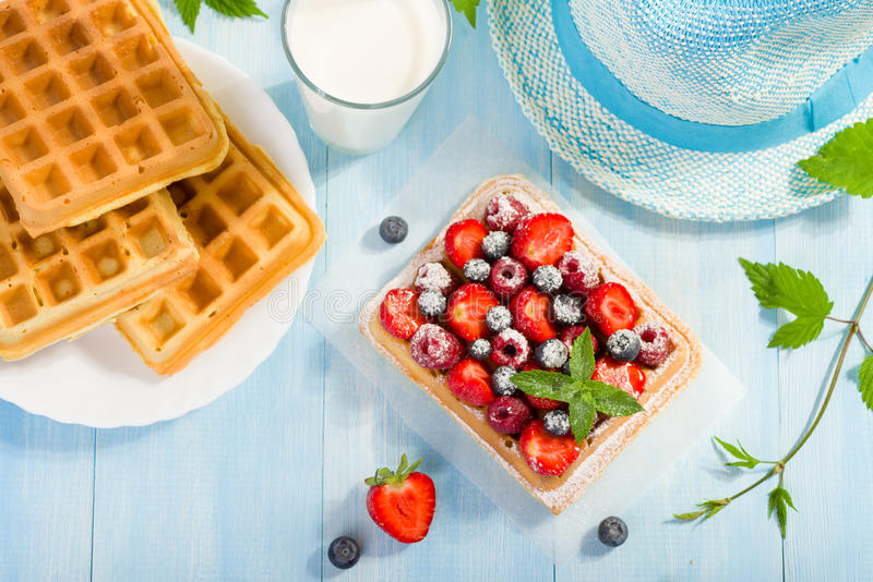 Waffles with strawberry and berry fruit. On blue table top view stock images