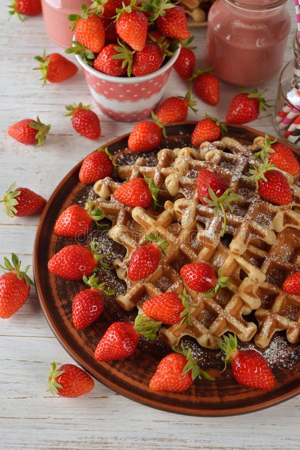 Waffles with strawberry. On a wooden background stock photography