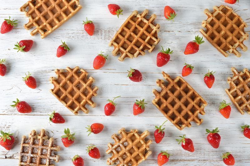 Waffles with strawberry. On a wooden background stock image