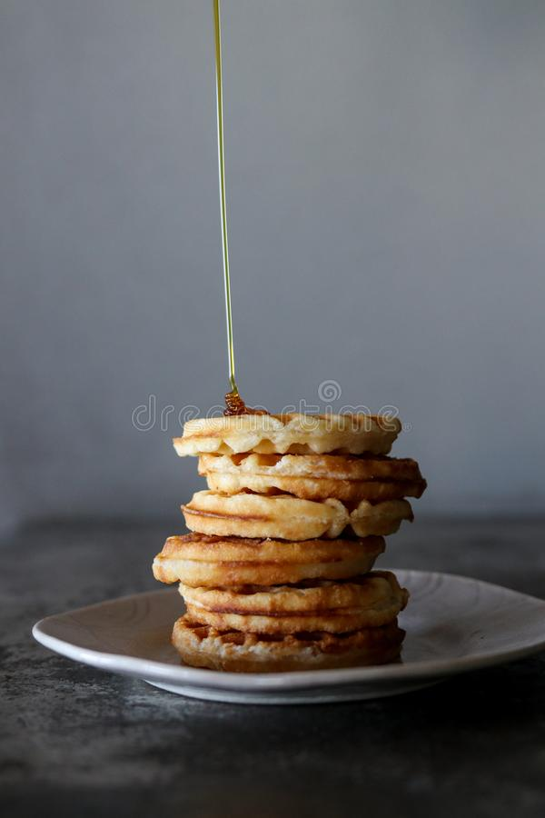 Waffles with Suryp. Waffles with Syrup being poured onto waffle royalty free stock photos