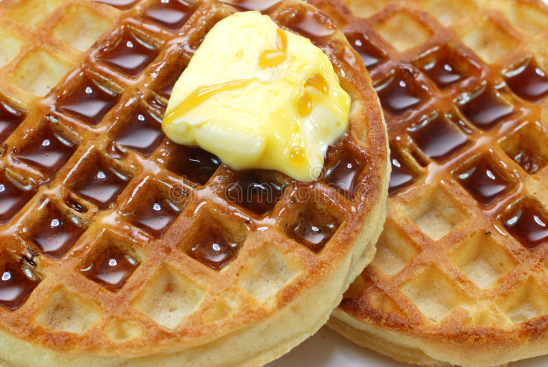 Waffles and Syrup Closeup. Closeup of waffles with syrup and butter royalty free stock photo