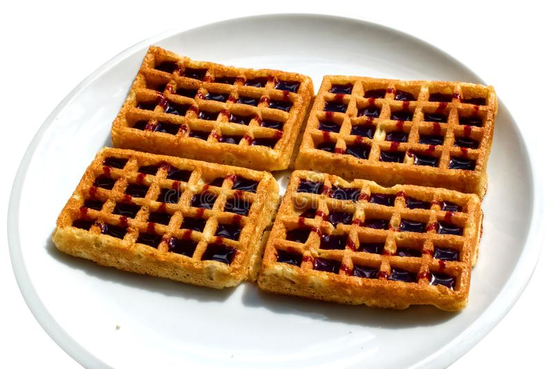 Waffles with syrup on the plate. Gold waffles with dark red syrup on a white plate. Image is isolated in white background. JPG and SVG stock illustration