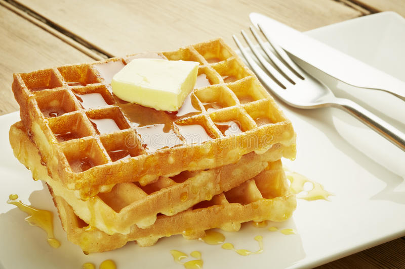 Waffles with syrup on white dish. And wooden table top royalty free stock images