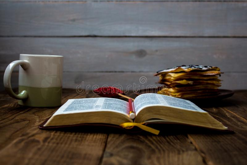Waffles and tea with bible. Waffles and tea and bible on wooden background stock image