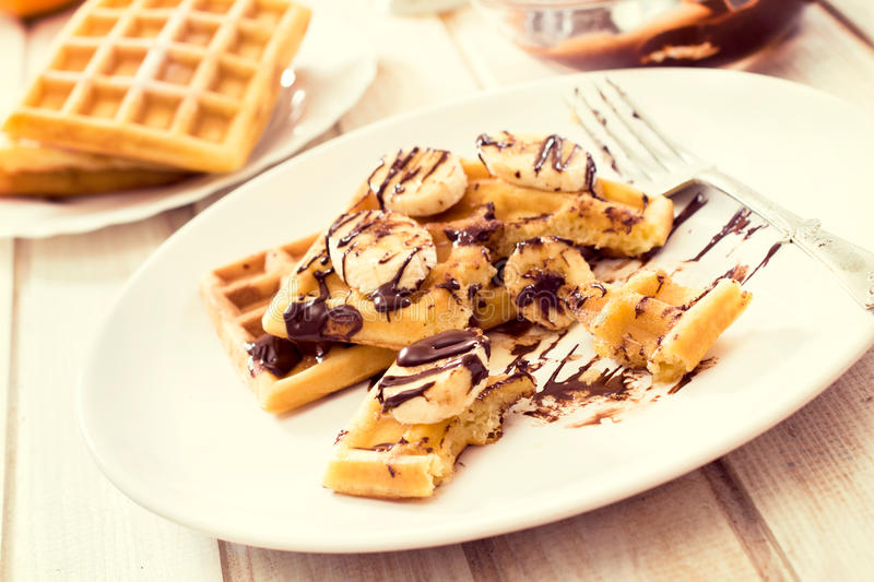 Waffles time. Selective focus on the front waffles in plate wit chocolate and bananas stock photography