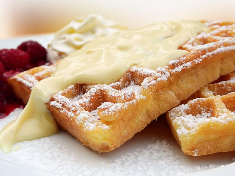 Waffles with vanilla and raspberries stock images