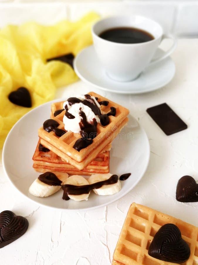 Waffles vienenses com gelado e xarope de chocolate na placa branca com café na tabela de madeira com corredor amarelo imagem de stock royalty free