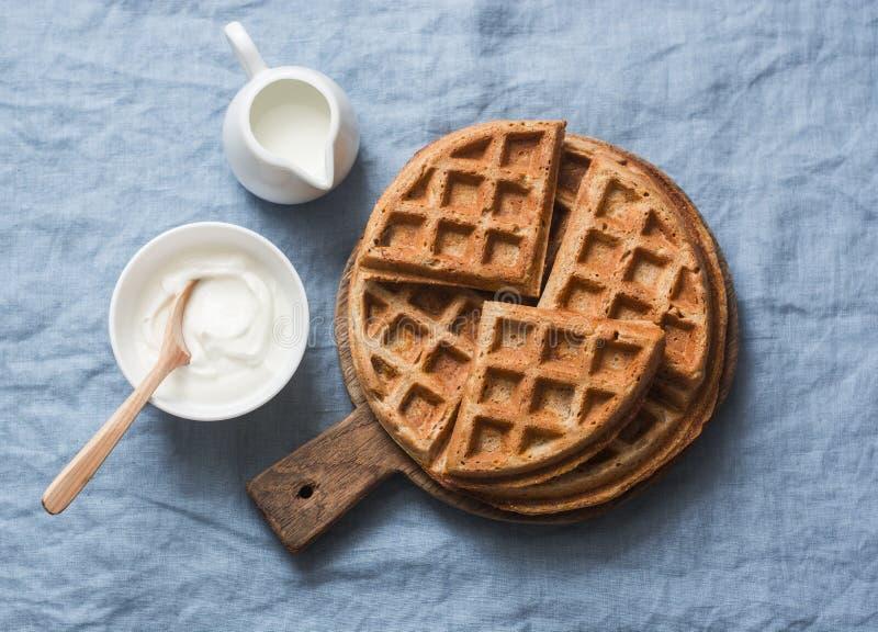 Waffles vienenses, creme e leite do café da manhã inteiro do trigo no fundo azul foto de stock