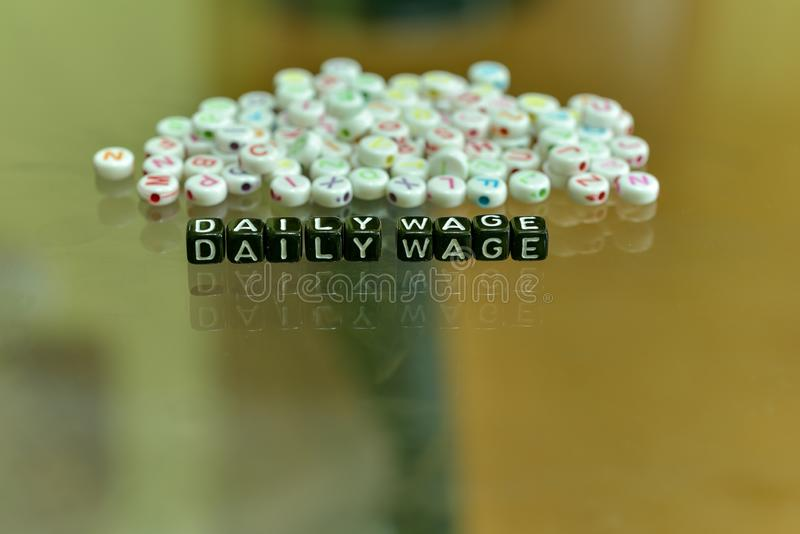 DAILY WAGE  written with Acrylic Black cube with white Alphabet Beads on the Glass Background.  stock images