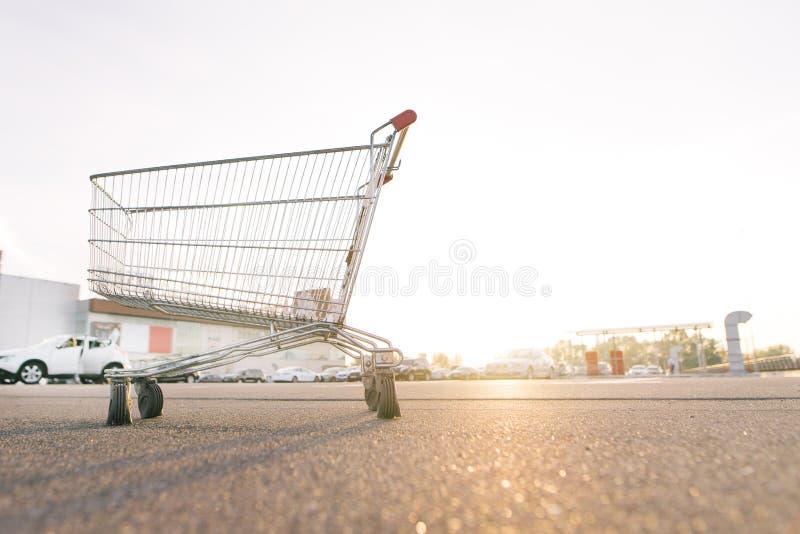 Wagen im Parkplatz nahe dem Einkaufszentrum bei Sonnenuntergang lizenzfreie stockbilder