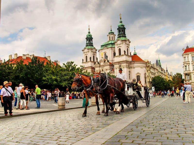 Wagen mit Pferden und Sankt- Nikolauskirche im alten Marktplatz in Prag, Tschechische Republik lizenzfreie stockbilder