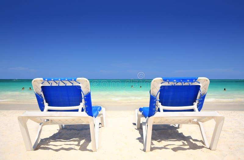 Wagenaufenthaltsraumstühle auf dem Strand stockbild