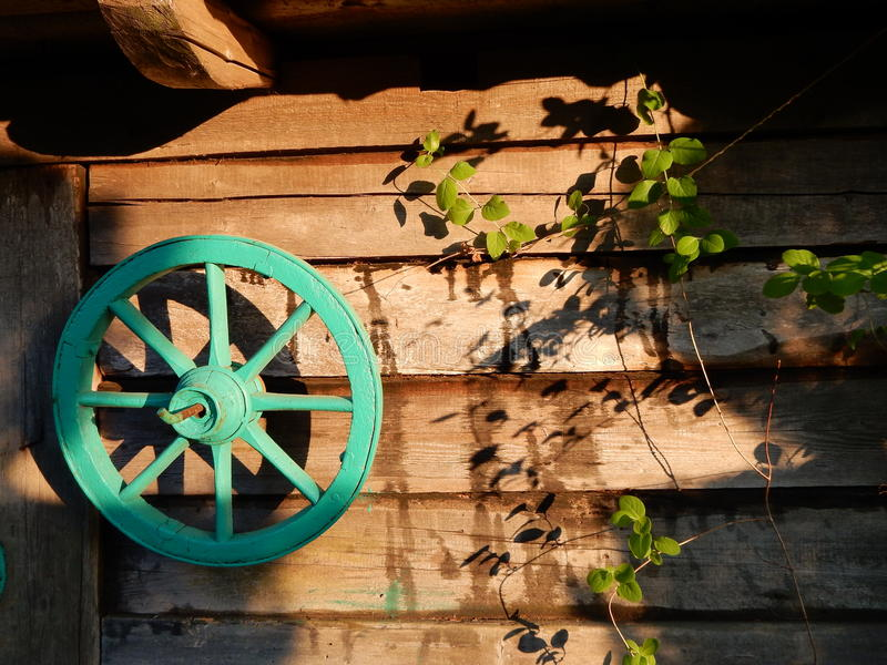 Wagenrad auf der Wand von hölzernen alten Planken stockfotografie