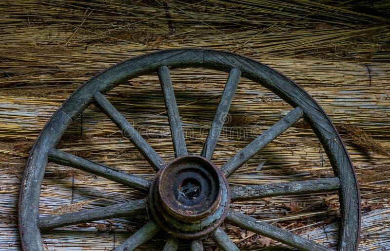 Wagenrad an der alten sraw Wand eines Hauses lizenzfreie stockbilder